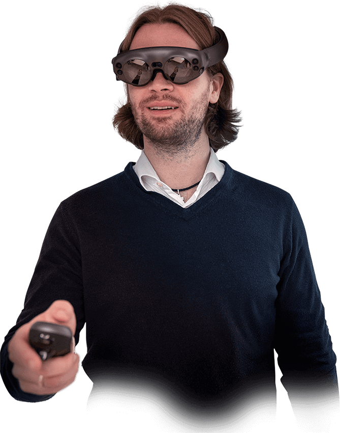 Alexander Bartella, MD, wears a mixed reality headset and holds the controller