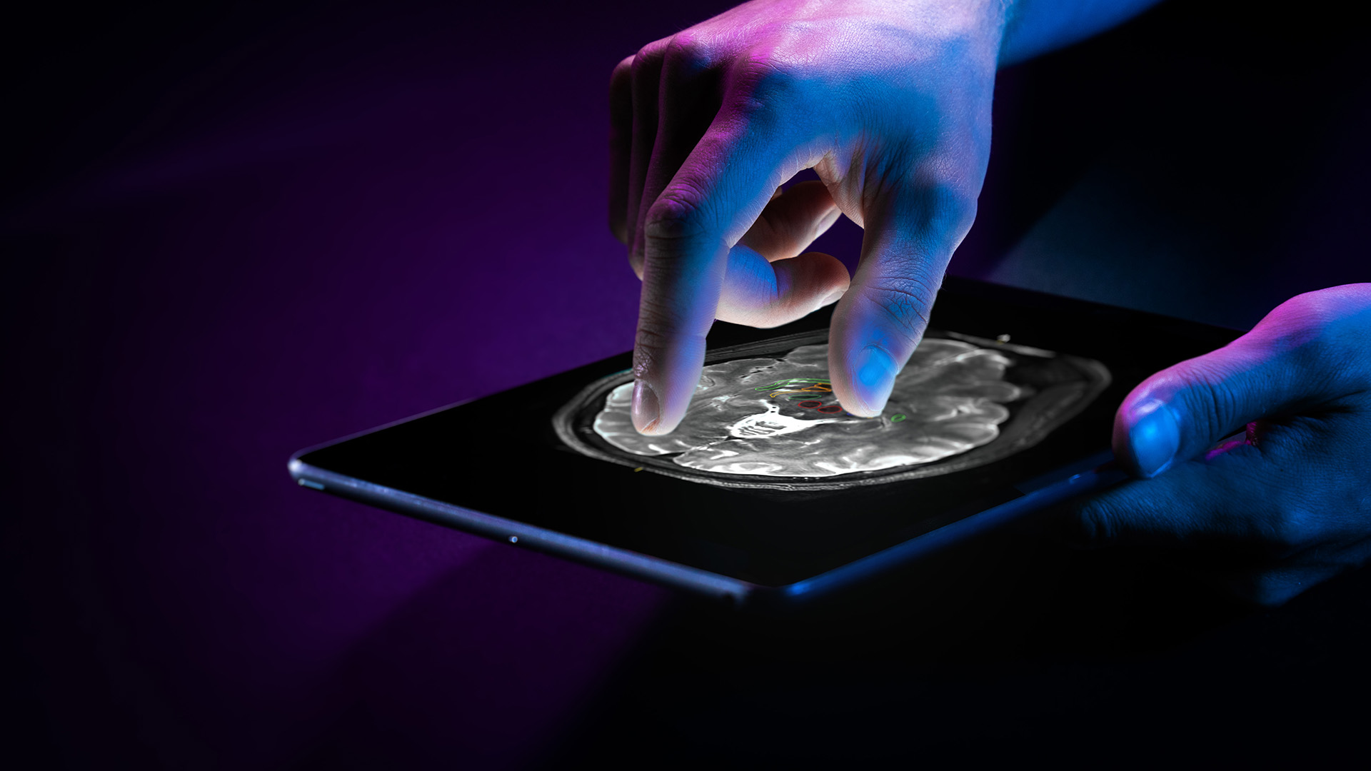 A hand holds a tablet while the other manipulates a digital patient scan on its touch screen