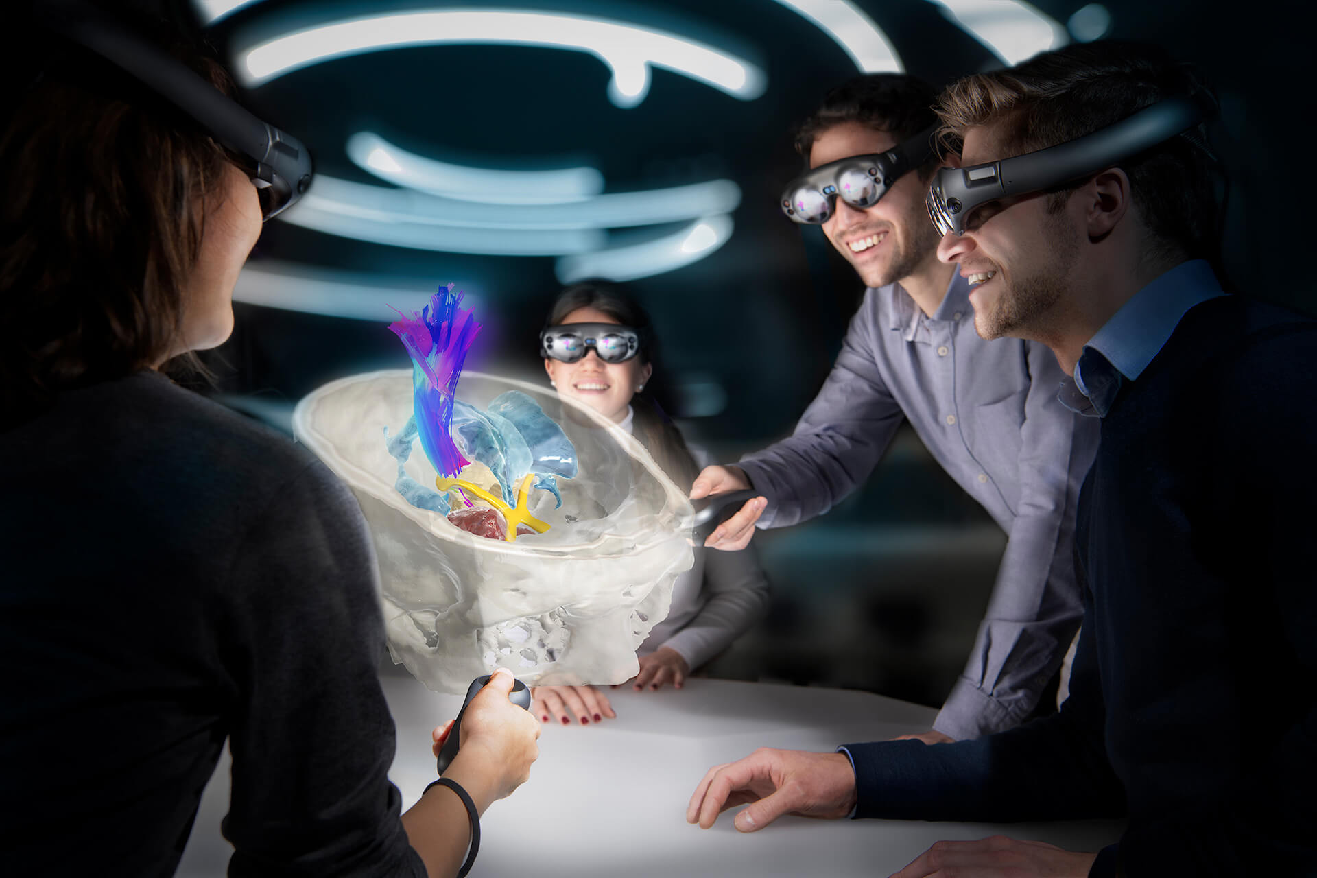 Four people wearing augmented reality glasses lean in around a table to examine a digital image of a skull and brain fiber tracts