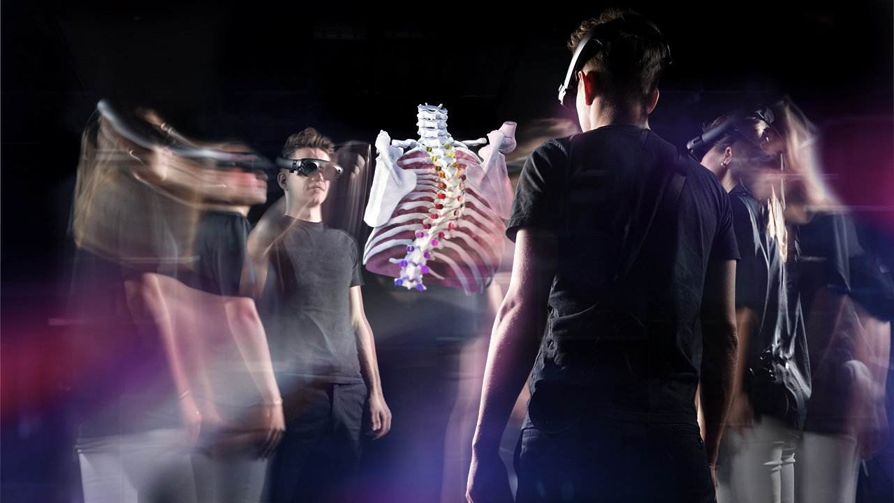 Three people wearing augmented reality glasses move around the digitally projected image of the bones of a human torso