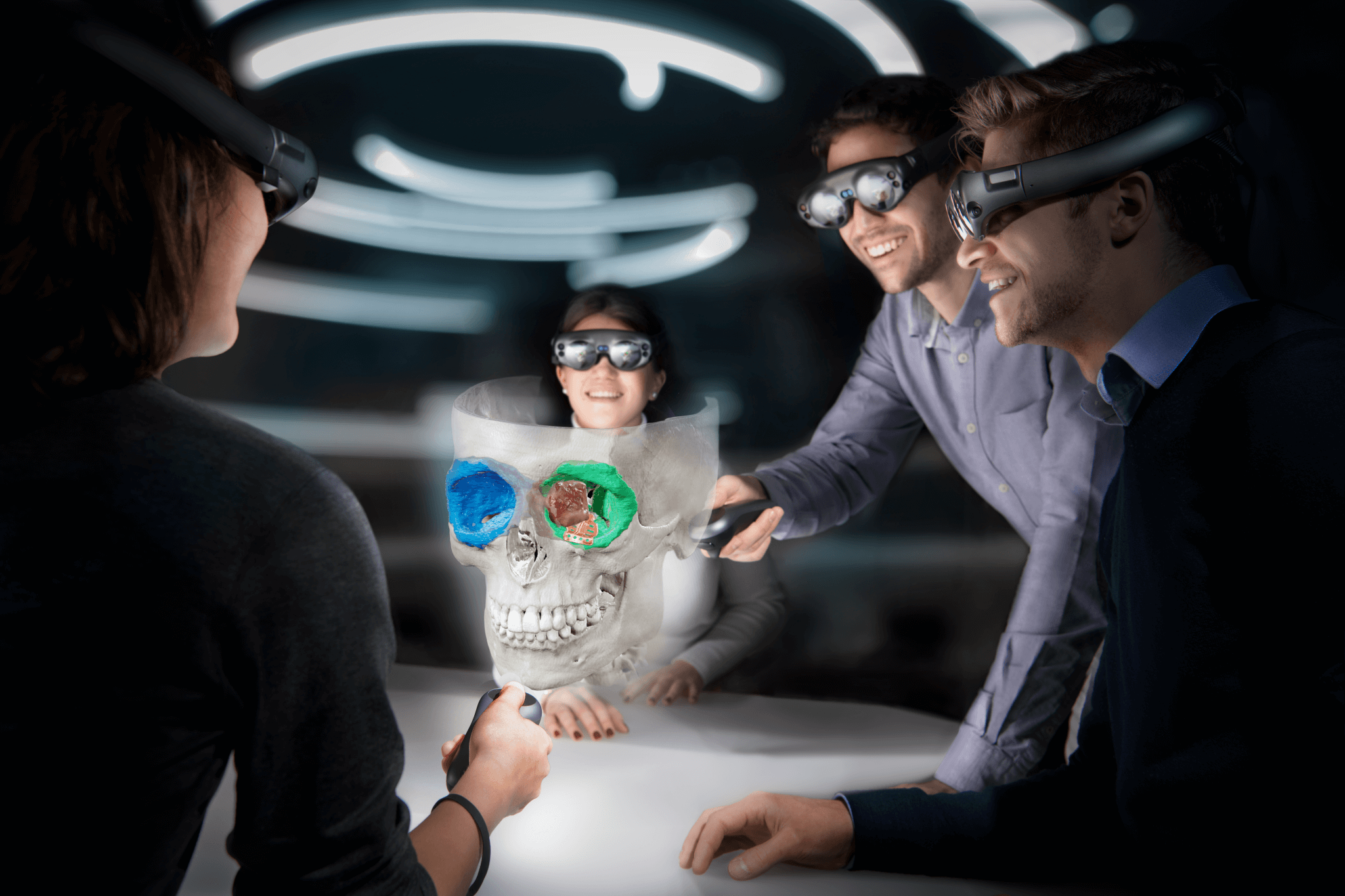 Tres personas con cascos Magic Leap se acercan para estudiar una proyección de realidad mixta de un cráneo con objetos segmentados para cirugía maxilofacial mientras una cuarta persona manipula la proyección con un controlador